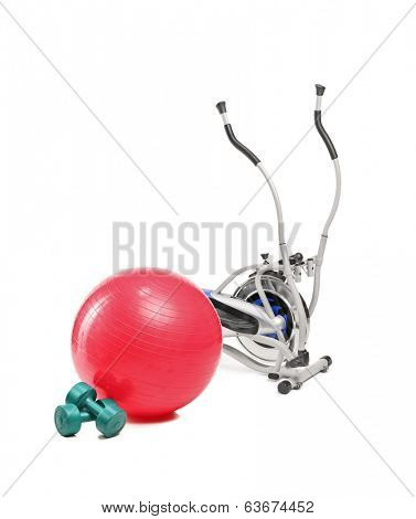 A studio shot of a cross trainer machine, pilates ball and dumbbells isolated on white background