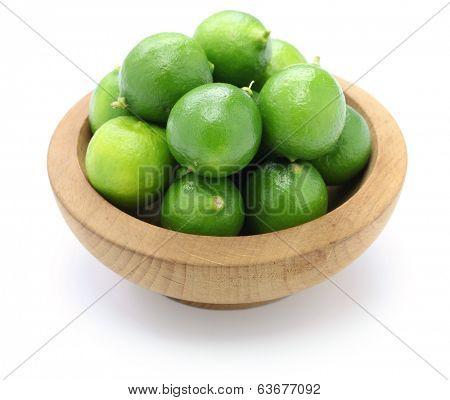 fresh key limes in wooden bowl