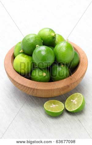 fresh key limes in wooden bowl