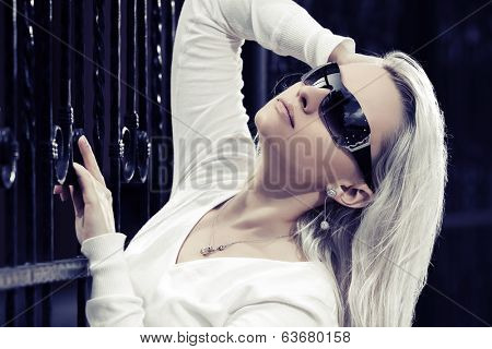 Blond fashion woman at the cast iron fence