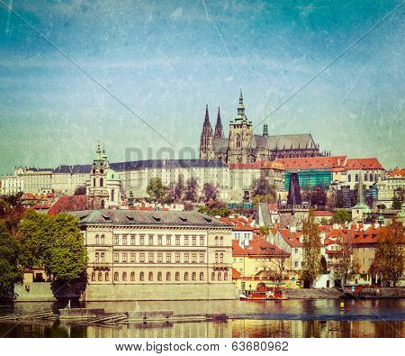 Vintage retro hipster style travel image of Charles bridge over Vltava river and Gradchany (Prague Castle) and St. Vitus Cathedral with grunge texture overlaid