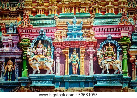 Vintage retro hipster style travel image of Shiva and Parvati on bull images. Sculptures on Hindu temple gopura (tower). Menakshi Temple, Madurai, Tamil Nadu, India