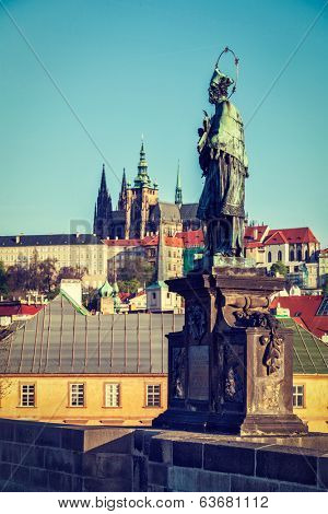 Vintage retro hipster style travel image of John of Nepomuk national saint of the Czech Republic statue on Charles Brigde at site where saint was thrown into Vltava with St. Vitus Cathedral in Prague
