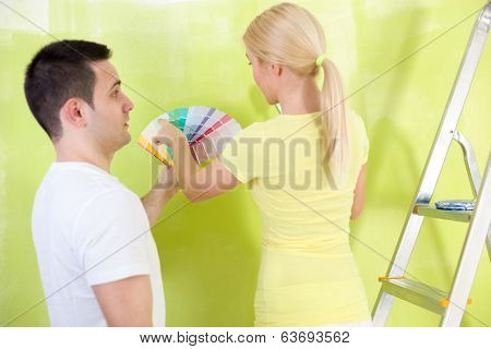 Couple choosing paint, man making face, he not like the chosen color
