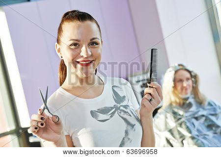 Happy female hairdresser with comb and scissors at beauty parlour with client