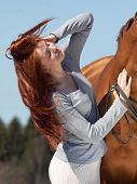 stock photo of horses ass  - Beautiful red haired girl and red horse - JPG