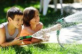 stock photo of fountain grass  - Happy kids playing and splashing with water sprinkler on summer grass yard - JPG