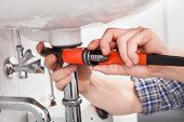 stock photo of adjustable-spanner  - Portrait of male plumber fixing a sink in bathroom - JPG
