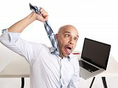 stock photo of choke  - bald south american businessman choking himself with his own tie while being over worked and stressed on this laptop on a white background - JPG
