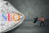 image of pulling  - Portrait of two business people pulling SEO banner