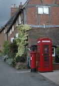 stock photo of postbox  - Old village scene with houses telephone and postbox - JPG