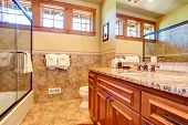 picture of tub  - Small bathroom with wooden cabinet and glass door bath tub - JPG