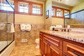 stock photo of bath tub  - Small bathroom with wooden cabinet and glass door bath tub - JPG