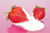 image of buttermilk  - Two strawberries in bed of buttermilk on a pink background - JPG