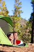 Camping couple in tent romantic looking at view in forest. Campers smiling happy outdoors in forest.