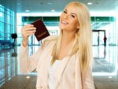 Happy blond woman with passport  in airport
