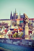 Vintage retro hipster style travel image of statue on Charles Brigde with St. Vitus Cathedral in bac