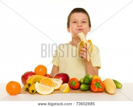 boy with fruits and vegetables eat banana