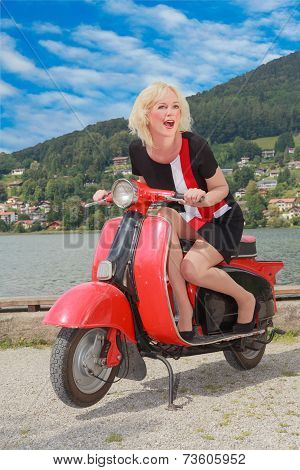 Young woman has fun on an old scooter