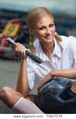 Girl  with helmet and screwdriver in Karting