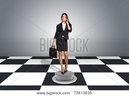 Beautiful businesswoman holding briefcase and using phone