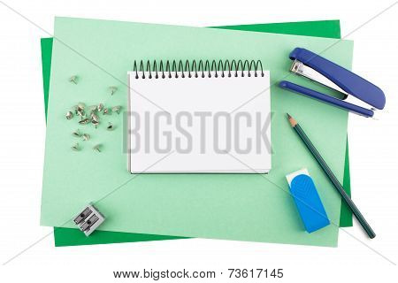 Office supplies on textured colored paper imitating a frame.