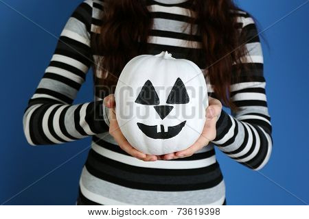 Woman holding decorative pumpkin, close-up