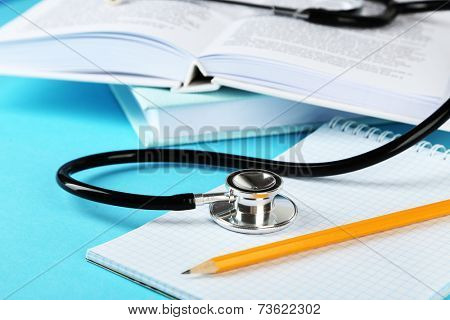 Medical stethoscope with notepad and books on blue background