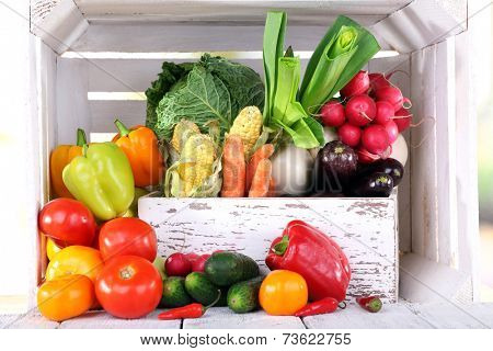Vegetables in wooden box on white wooden box background
