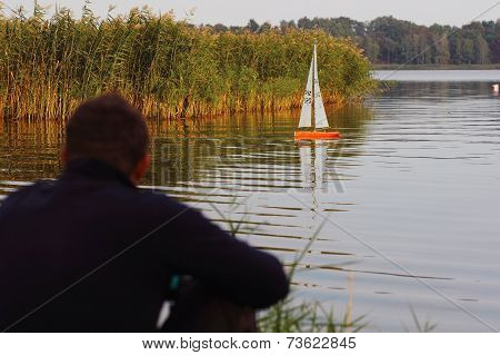 man watching a radio-controlled boat