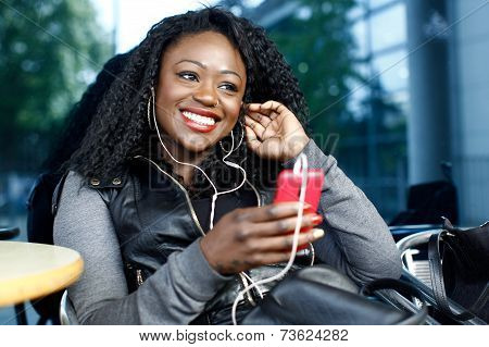 African Woman Listening To Music Outdoors