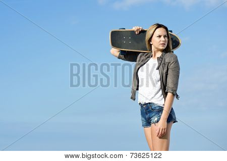 Pretty girl carrying a skateboard on her shoulder, looking back. Plenty of copy space.