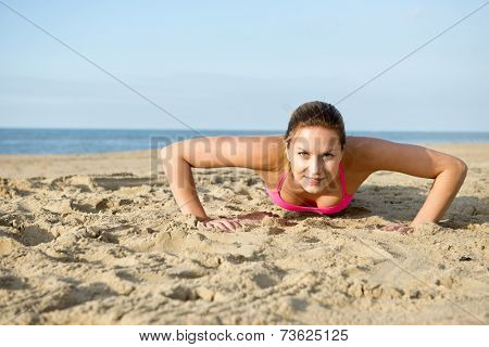 Fit, athletic, woman doing push ups during a workout on a sandy beach
