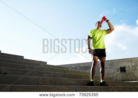 Athletic build runner resting drink energy drink after run