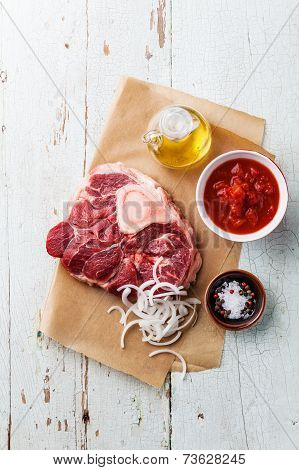 Raw Fresh Cross Cut Veal Shank And Ingredients For Making Osso Buco On Blue Background