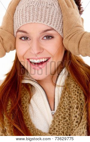 Vivacious gorgeous young woman in winter fashion laughing as she holds her gloved hands to her knitted beanie hat