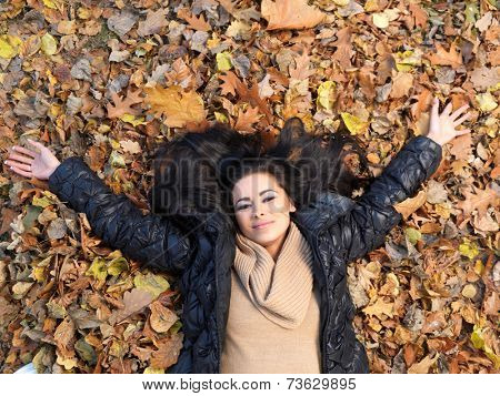 Woman lying on her back in autumn leaves with her arms extended and long brunette hair spread around her face smiling up at the camera