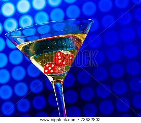 Red Dice In The Cocktail Glass On Blue Bokeh