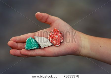 Child hand holding colored stones