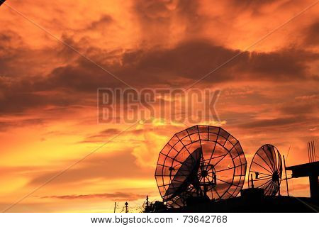 Satellite dishes in sunset