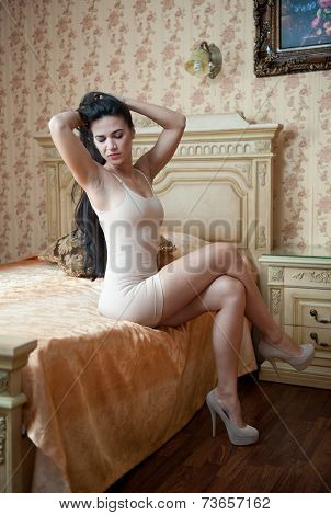 Young beautiful sexy woman in white short tight dress posing challenging indoor in vintage hotel