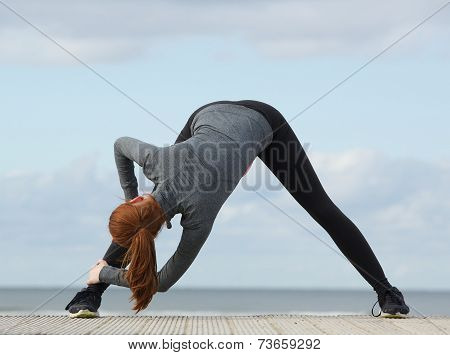 Sporty Woman Bending Down And Stretching Exercise