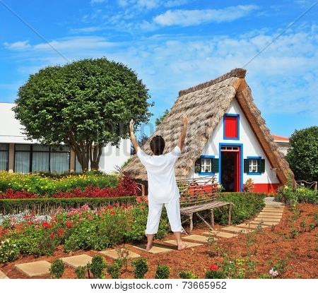 The charming rural lodge with a triangular roof. The slender elderly woman in a white suit for yoga carries out an asana