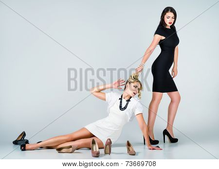Studio Fashion Shot: Confrontation Of Two Cute Women (blonde And Brunette)