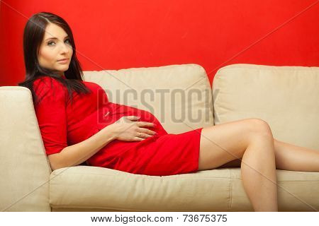 Pregnant Woman Relaxing On Sofa Touching Her Belly