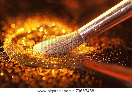 Close-up on brush and gold shining powder