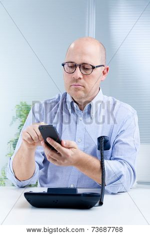 Upright Nerdy Clerk With Two Telephones