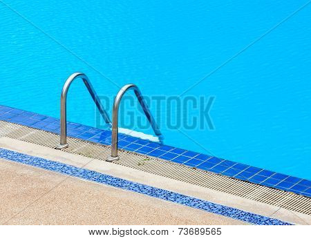 A View Of A Light Clear Blue Swimming Pool With Steel Ladder.