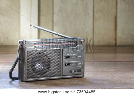 Old Transistor Radio On Wooden Background.