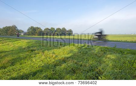 Motorcyclist driving over a road at fall
